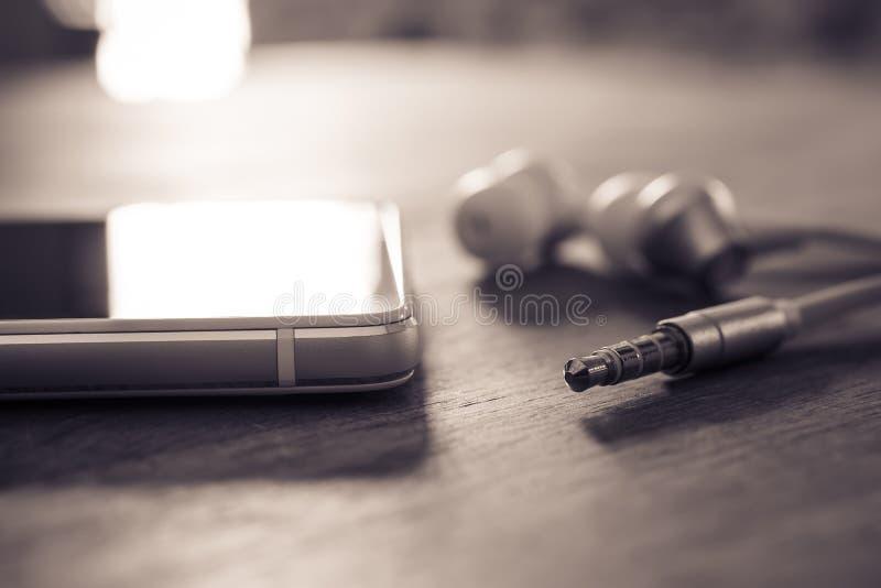 Наушники и кабель В-уха лежа рядом с белым мобильным телефоном в Monochrome цветах стоковая фотография rf