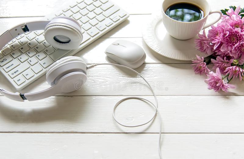 Наушники и кофейная чашка на деревянной таблице стола с розовым цветком Концепция музыки и образа жизни стоковая фотография