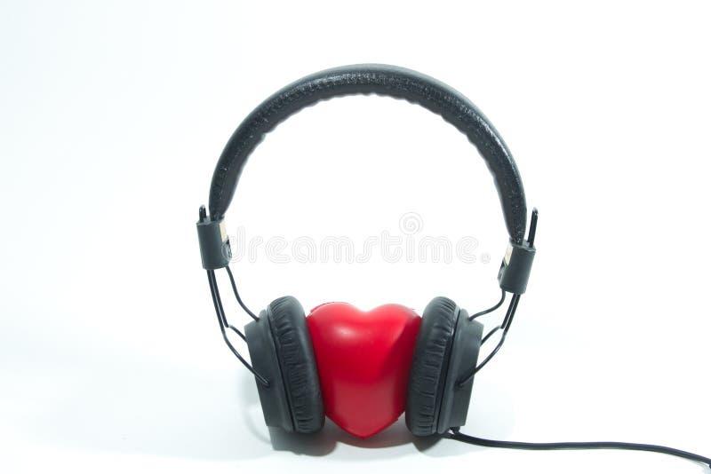 Наушники и красная концепция сердца для влюбленности слушая к музыке дальше стоковые изображения rf