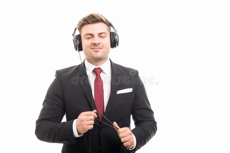 Наушники молодого менеджера нося наслаждаясь музыкой стоковое изображение rf