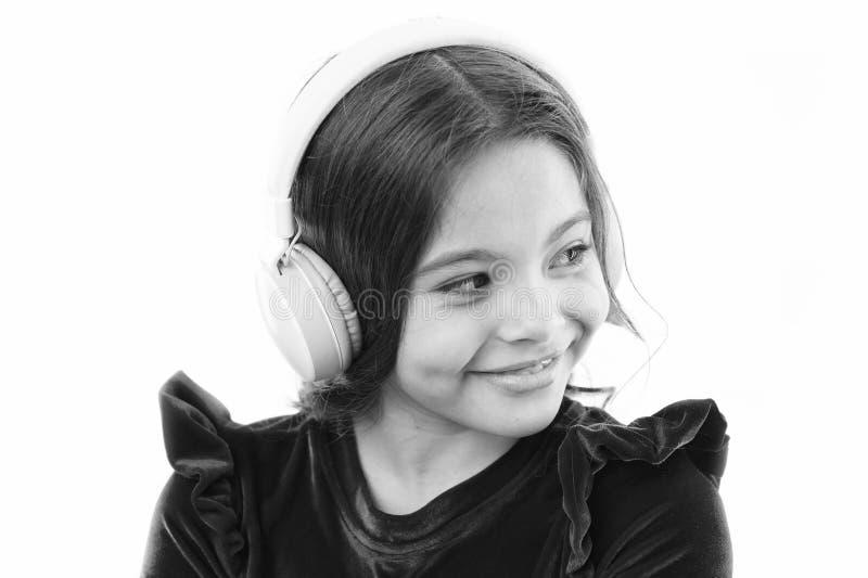 Наушники музыки пользы маленького ребенка девушки современные Слушают бесплатно новые и предстоящие популярные песни прямо сейчас стоковое фото rf