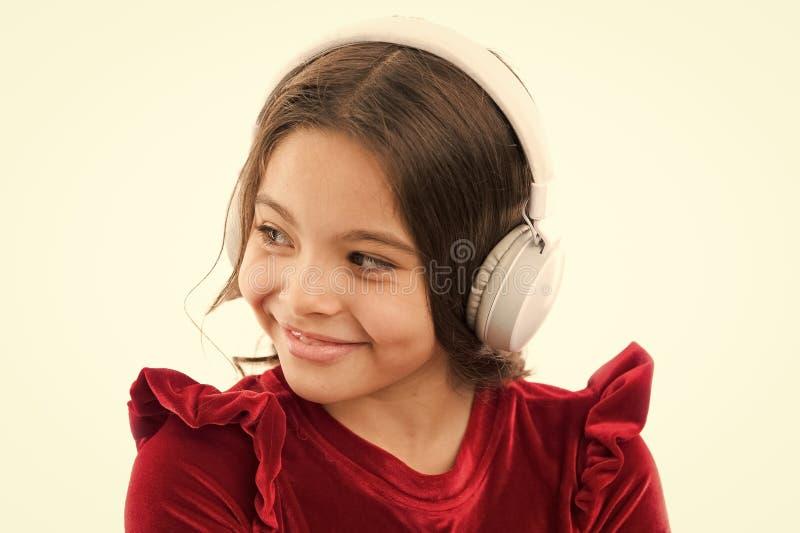 Наушники музыки пользы маленького ребенка девушки современные Слушают бесплатно новые и предстоящие популярные песни прямо сейчас стоковые фотографии rf
