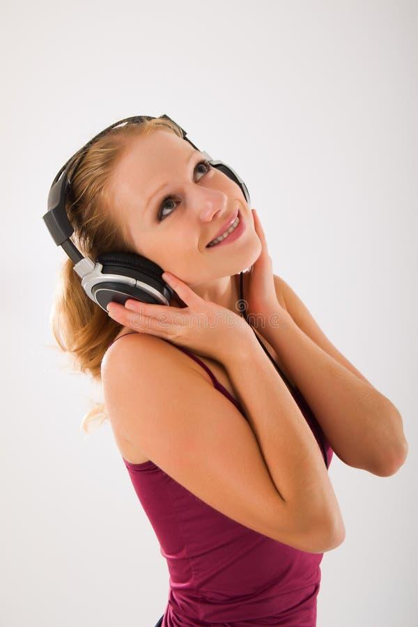 наушники привлекательной девушки счастливые слушают mus к стоковое изображение