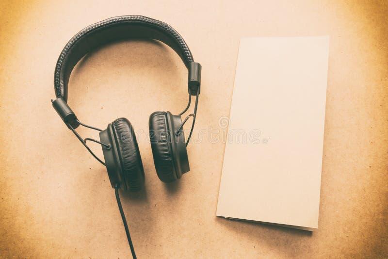 Наушники с коричневым цветом и примечание белой бумаги на деревянном столе в студии музыки стоковое изображение rf