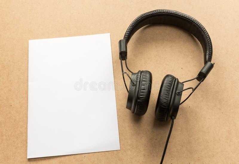 Наушники с примечанием белой бумаги на деревянном столе стоковые фото