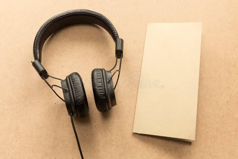 Наушники с примечанием коричневой бумаги на деревянном столе стоковая фотография rf
