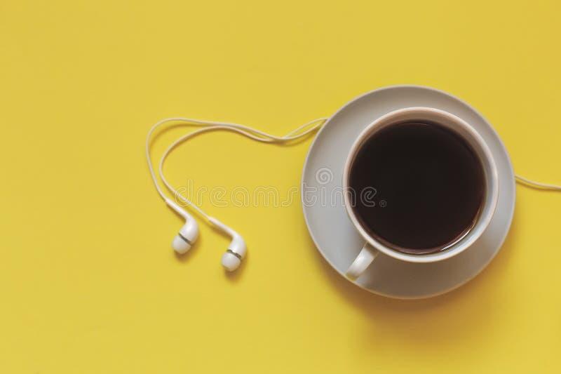 Наушники чашки кофе или чая и белизны на желтой предпосылке, тонизированном взгляд сверху, стоковые фотографии rf