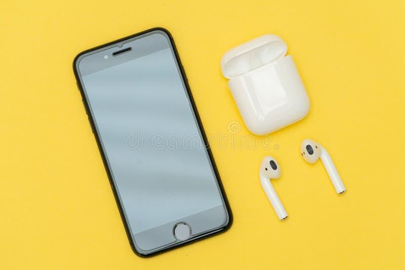 Наушники AirPods беспроволочные наушниками AppleAirPods беспроволочными Яблоком с iPhone стоковое изображение