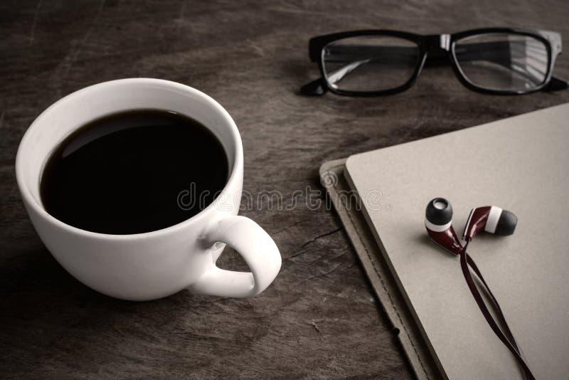 Наушник с кофе и тетрадью на старом деревянном столе стоковое изображение