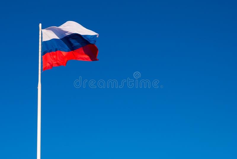 Национальный флаг России на ветре флагштока порхая против голубого неба Россия стоковая фотография