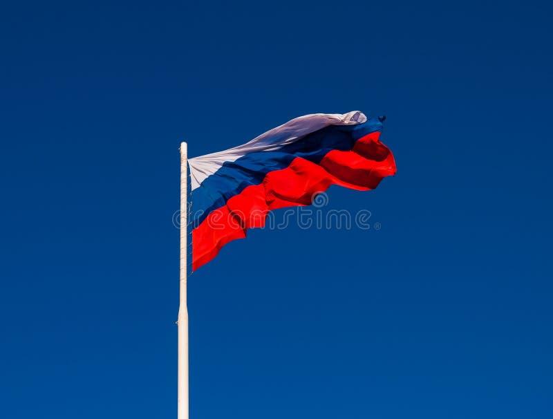 Национальный флаг России на ветре флагштока порхая против голубого неба Россия стоковые фотографии rf