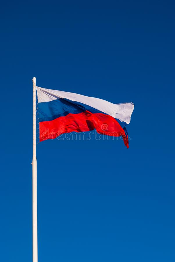 Национальный флаг России на ветре флагштока порхая против голубого неба Россия стоковая фотография rf