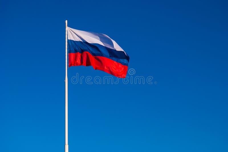Национальный флаг России на ветре флагштока порхая против голубого неба Россия стоковое фото rf