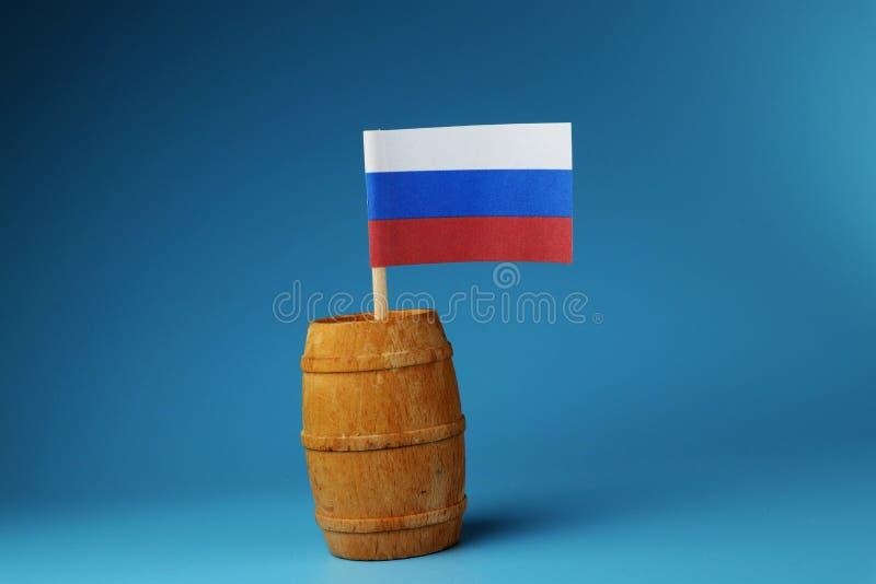 Национальный флаг России на деревянной ручке в деревянном бочонке на голубой предпосылке стоковые фотографии rf
