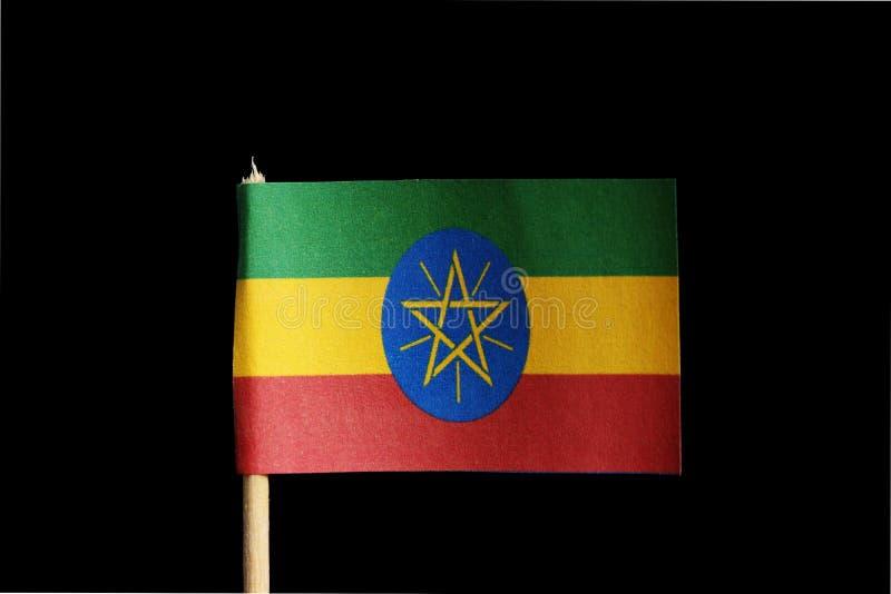 Национальный флаг Эфиопии на зубочистке на черной предпосылке Состоит из 3 традиционных цветов зеленого, желтого и красный цвет и стоковое фото