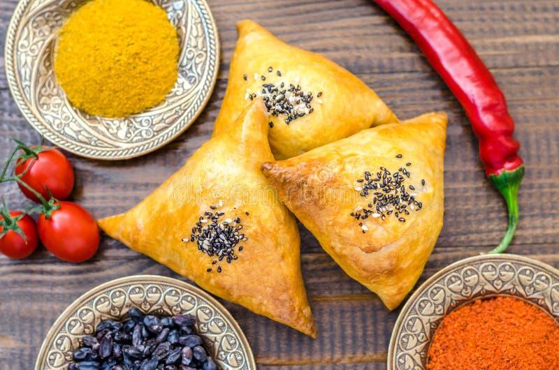 Национальные узбекские блюда samsa, томаты, красный пеец и condiments стоковые фотографии rf