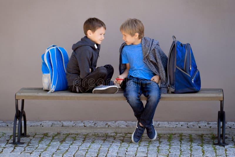 Начальное образование, школа, концепция приятельства - 2 мальчика при рюкзаки сидя, разговаривая и играя с обтекателем втулки стоковые фотографии rf