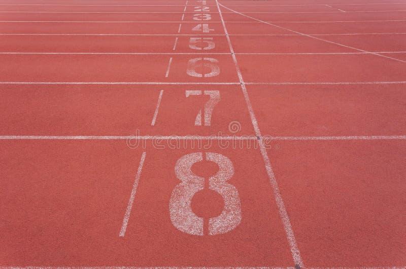 Начинающ майну с номерами на красном идущем следе для атлетики стоковое изображение