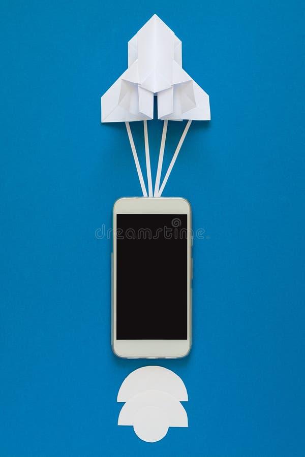 Начните вверх или быстрая концепция соединения Ракета бумаги старта с умным телефоном на голубом небе с облаками стоковые фотографии rf