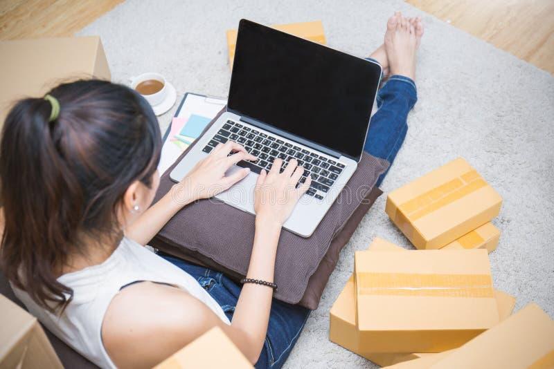 Начните вверх МАЛЫЕ И СРЕДНИЕ ПРЕДПРИЯТИЯ предпринимателя мелкого бизнеса или работать азиатская женщина работая с коробкой стоковое фото rf