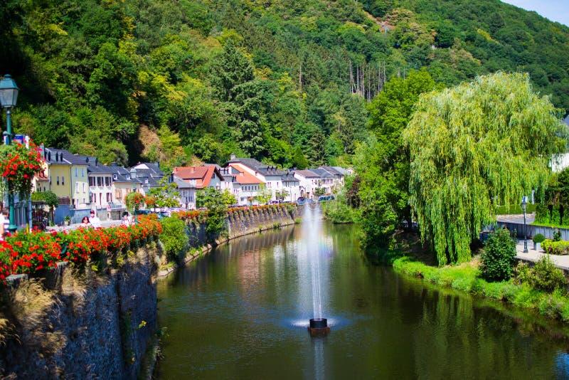 Наш переход через реку старый городок Vianden, Люксембурга, с типичными домами, деревьями и горой на предпосылке стоковое фото