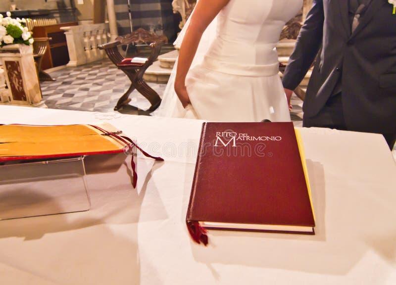 На алтаре книга свадьбы приветствует детенышей пожененные пары стоковые фото
