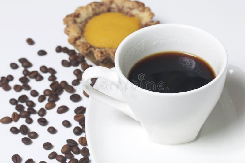 На белой поверхности таблицы чашка душистого кофе на поддоннике Торт рядом Следующие разбросанные кофейные зерна стоковое изображение rf