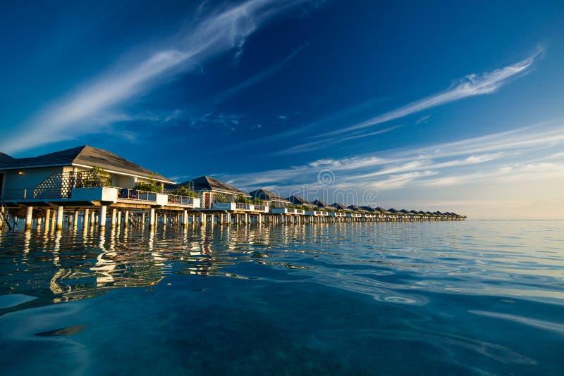 Над водой виллы в Мальдивах отразили в голубой лагуне стоковое фото rf