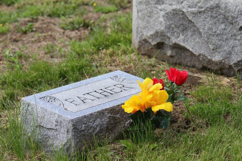 Надгробная плита с отцом и цветками стоковое фото rf