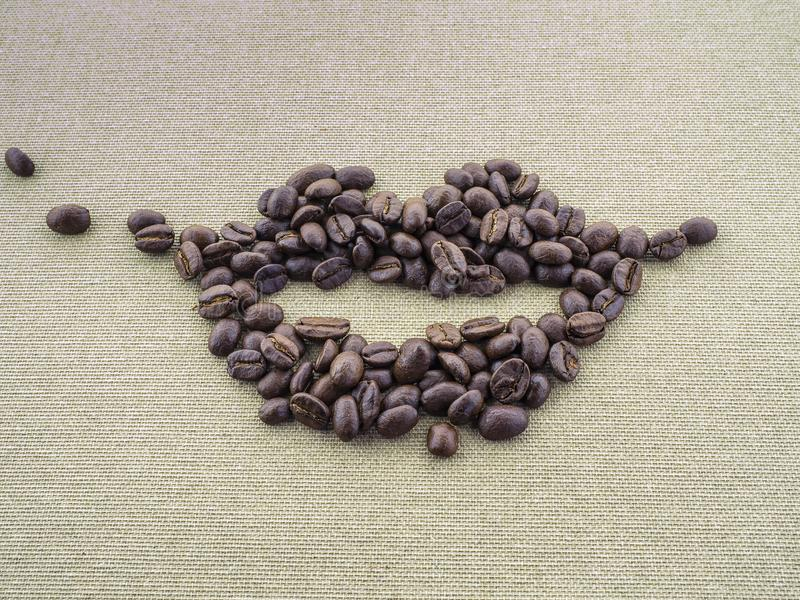 На грубом applique linen холста от зажаренных в духовке кофейных зерен в форме губ рта персоны Улыбка стоковые изображения