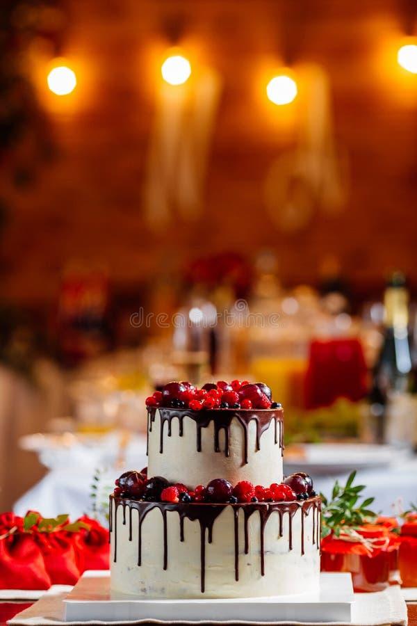 На двух уровнях белый украшенный свадебный пирог, при свежие красные плодоовощи и ягоды, облитые в шоколаде Яркое украшение табли стоковая фотография rf