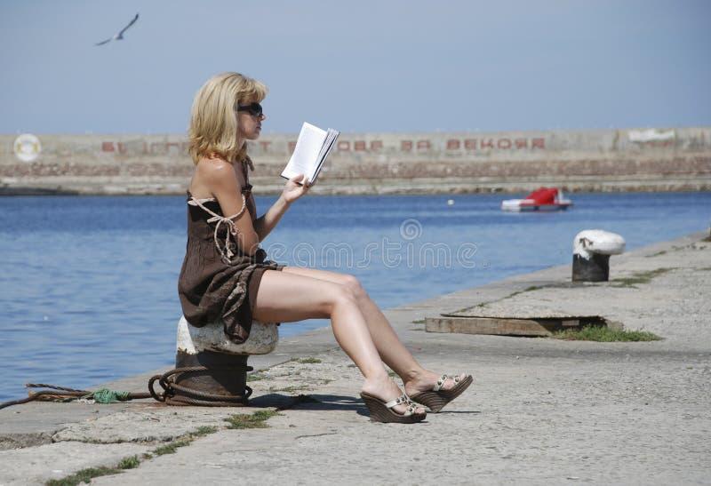 На девушке пристани читая книгу и загорать стоковое фото rf