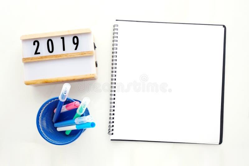2019 на деревянной коробке, пустая бумага тетради на белом мраморном bac таблицы стоковые изображения rf
