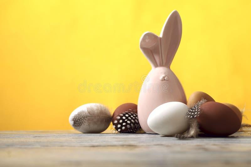 На деревянной поверхности кролик пасхи веселый и коричневые и белые яйца, желтая предпосылка стоковое фото rf