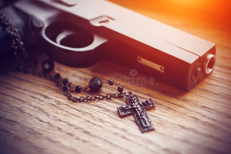 На деревянной поверхности лежат черное оружие и черный крест на цепи стоковое фото rf