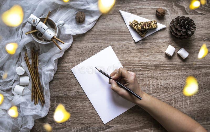 На деревянной предпосылке лист и ручка пишут, зефиры и помадки, кружка с какао, лож расплавленный снеговик сделанный marshmallo стоковая фотография rf