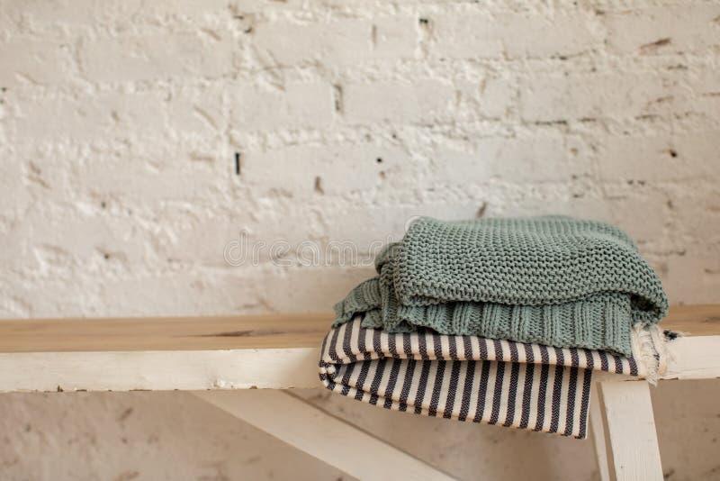 На деревянной скамеечке сложены одеяла стоковая фотография rf