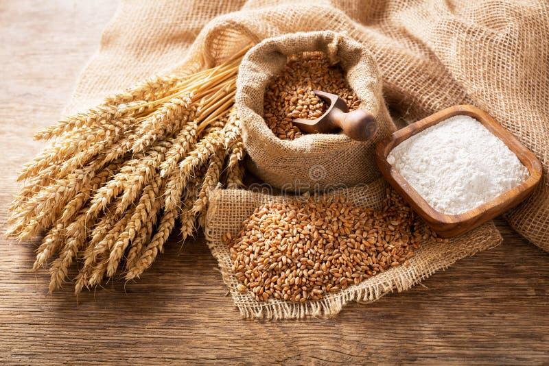 На деревянном столе висят колбасы, зерна и мука стоковая фотография
