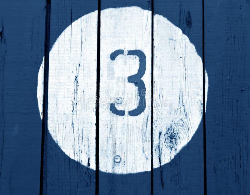 3 на деревянной голубой тонизированной стене стоковые изображения rf