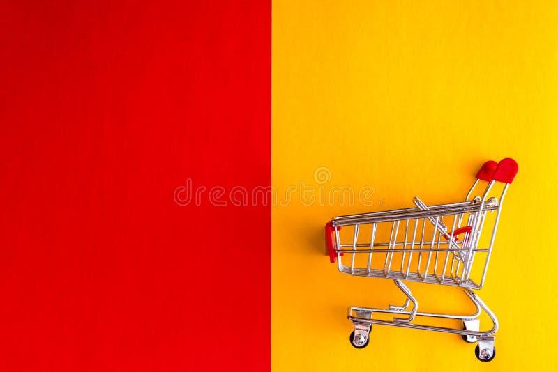 На желт-красной предпосылке, тележк-корзине бакалеи и вопросительном знаке ( Концепция, выбор покупок стоковые фото