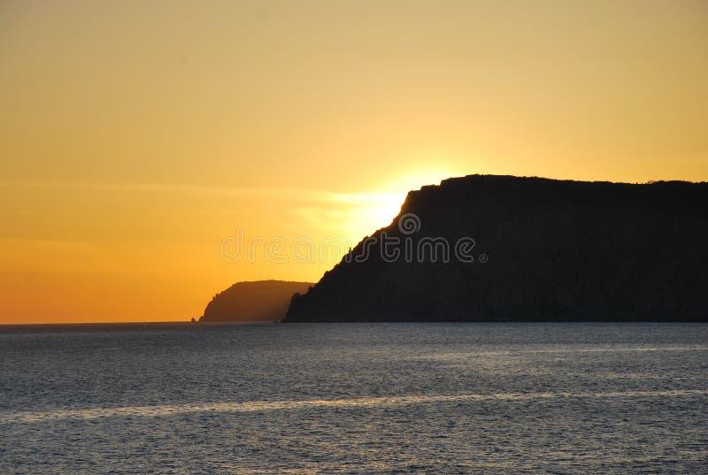 над желтым цветом захода солнца океана склонения эффективным стоковое фото rf