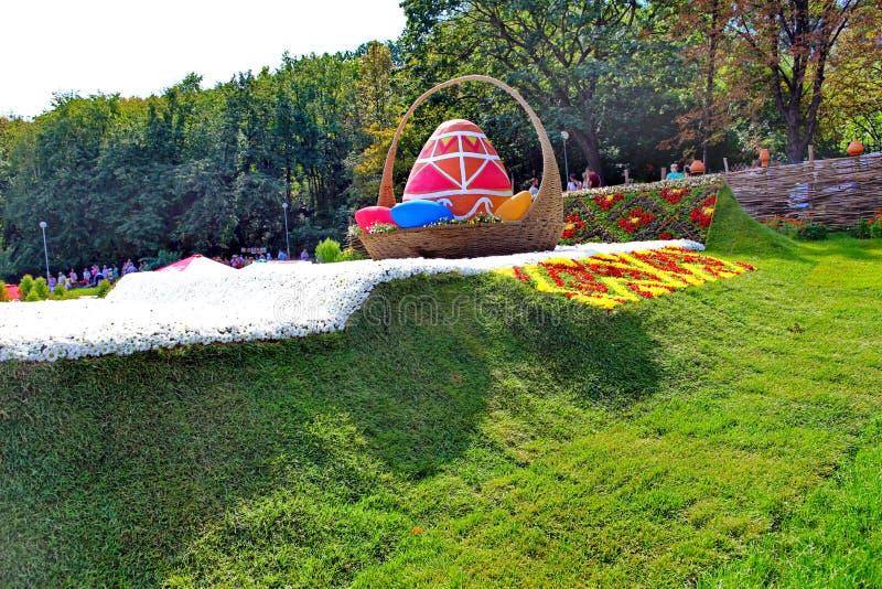 На зеленой лужайке в парке выставка на теме народных обычаев Высокорослое яичко украшенное с картинами в лозе стоковые изображения rf