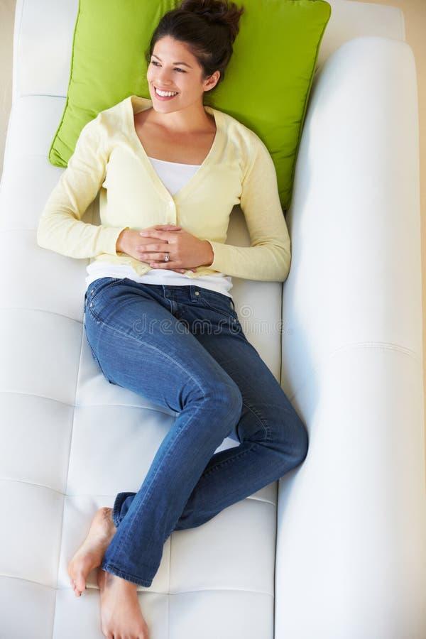 Надземный взгляд женщины ослабляя на софе смотря телевидение стоковые изображения
