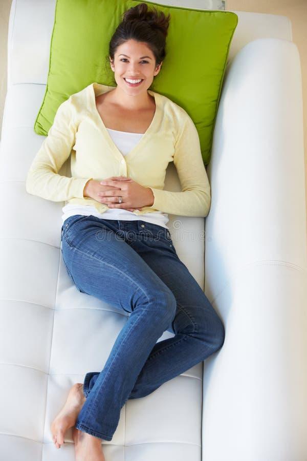 Надземный взгляд женщины ослабляя на софе стоковая фотография