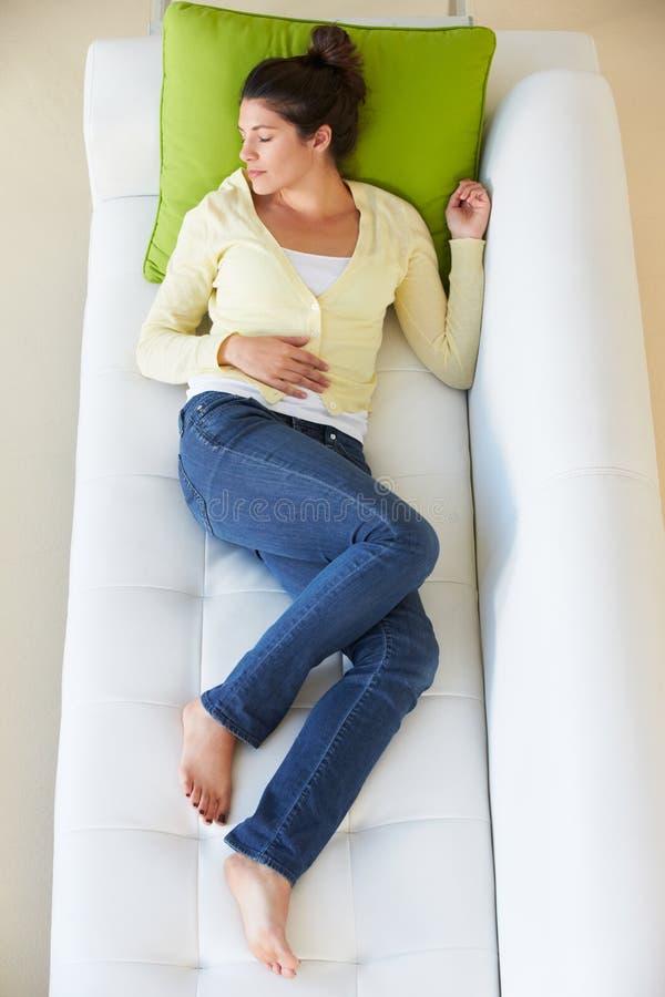 Надземный взгляд женщины ослабляя на софе стоковое изображение rf