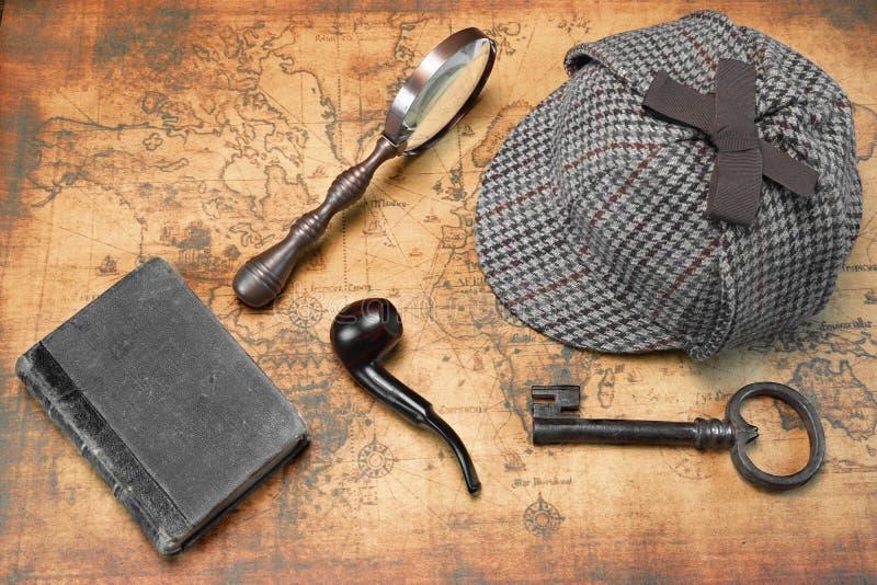 Надземный взгляд инструментов шляпы и сыщика Sherlock на карте стоковые фото
