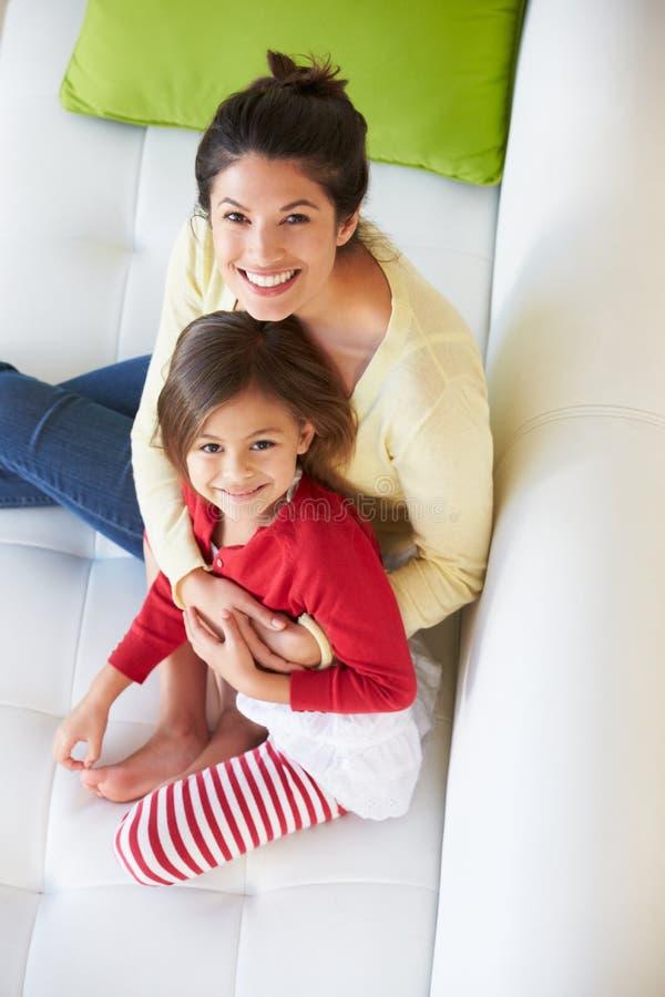 Надземный взгляд матери и дочери ослабляя на софе стоковое фото rf