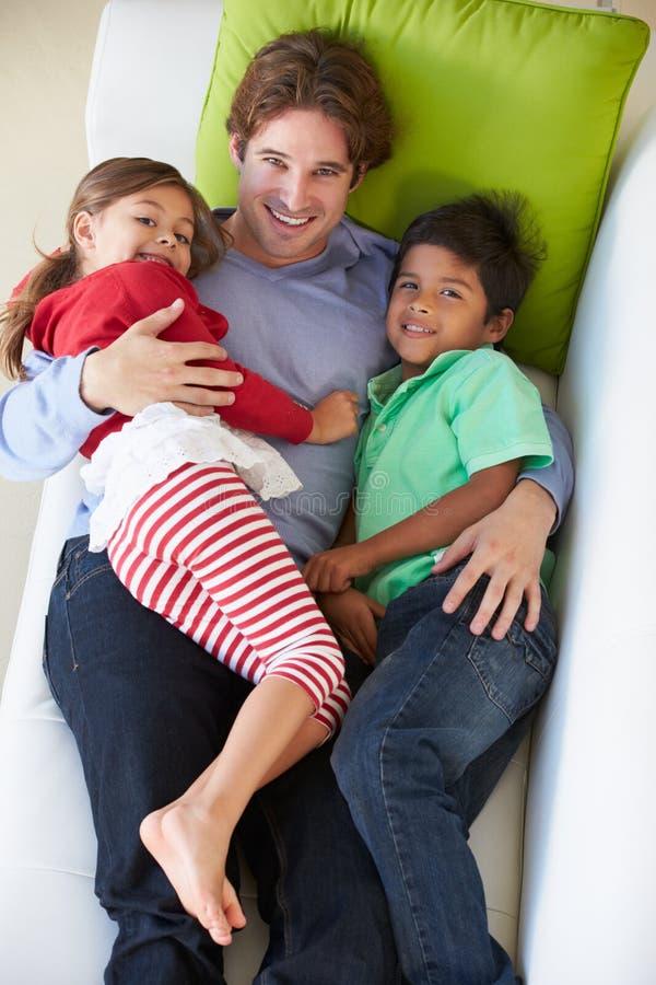 Надземный взгляд отца и детей ослабляя на софе стоковая фотография rf