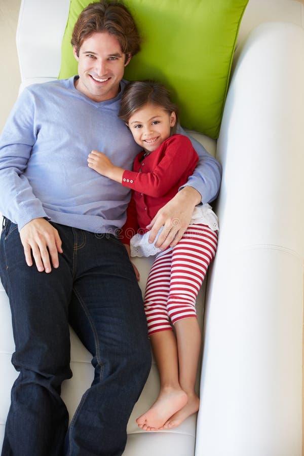 Надземный взгляд отца и дочери ослабляя на софе стоковые фото