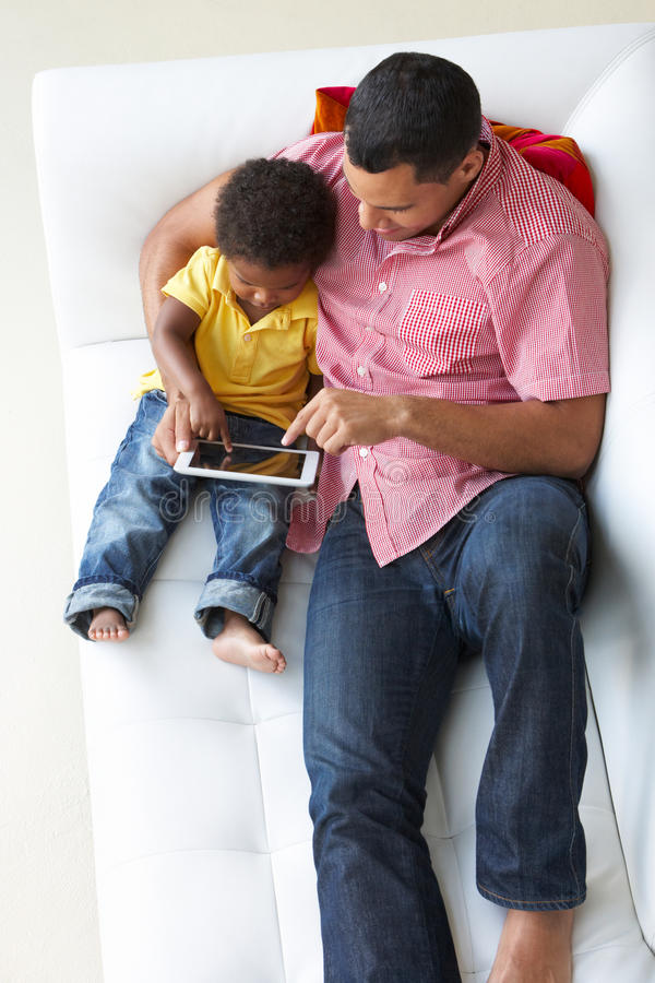 Надземный взгляд отца и сына на софе используя таблетку цифров стоковые изображения